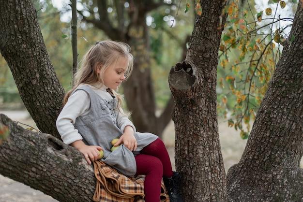 Kind appels plukken op boerderij in de herfst. het spelen van het meisje in de boomgaard van de appelboom. gezonde voeding.