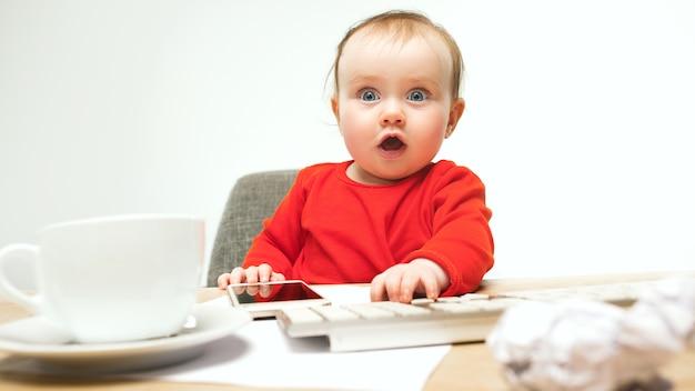 Kind babymeisje zit met toetsenbord van moderne computer of laptop in witte studio.