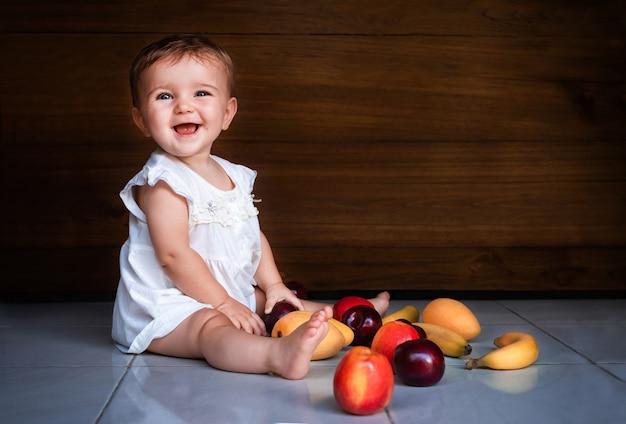 Kind babymeisje zittend op de vloer met fruit en lachend op houten achtergrond