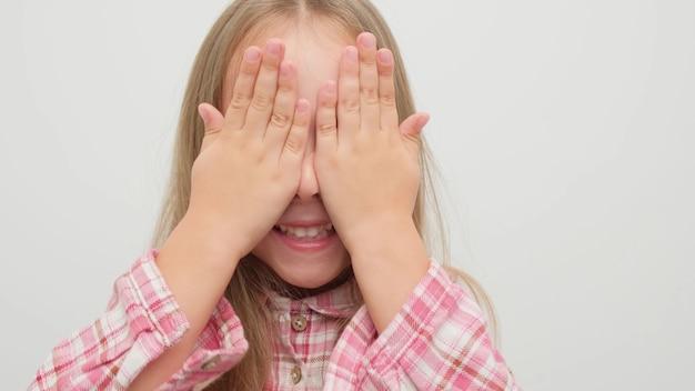 Kind bedekt haar gezicht met haar handen