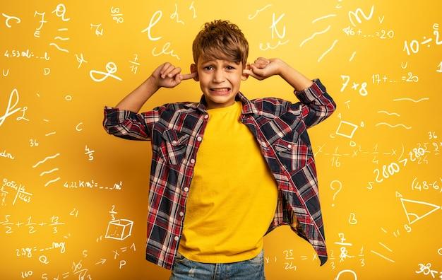 Kind bedekt zijn oren omdat hij geen rekenkundige uitleg wil horen