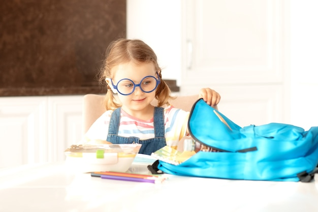 Kind bereidt rugzak voor op school op zonnige ochtend keukenonderwijslerenterug naar school