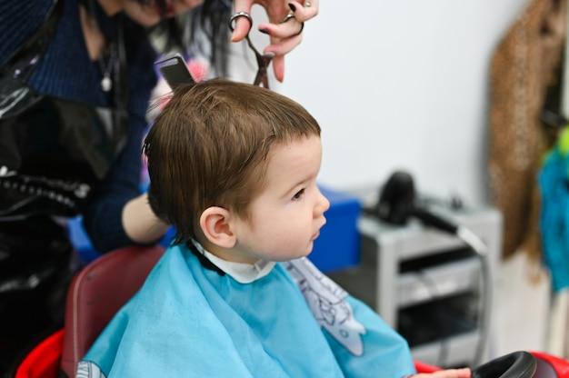 Kind bij de kapper close-up. het eerste kapsel van het kind bij de kapper. baby kapsel peuter.