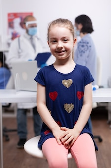 Kind bij medisch onderzoek in ziekenhuiskantoor tijdens wereldwijde pandemie