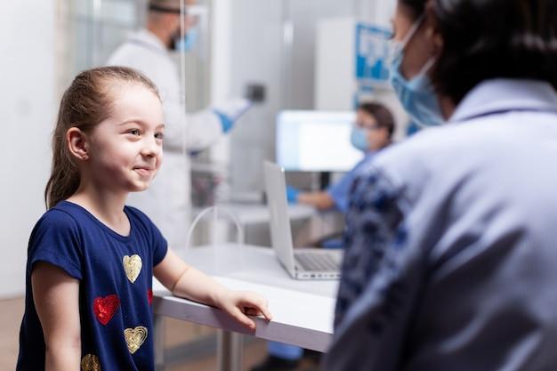 Kind bij ziekenhuisoverleg met moeder tijdens wereldwijde pandemie. arts die gezichtsmasker draagt. specialist in geneeskunde die consultatie van gezondheidszorgdiensten verleent, radiografische behandeling in de kliniek.