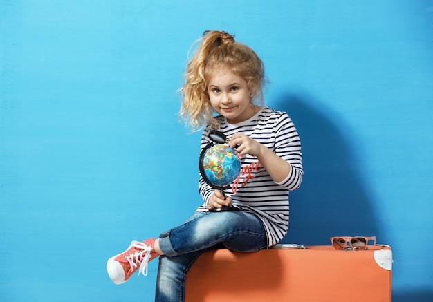 Kind blond meisje met roze vintage koffer bestudeert de hele wereld. reizen en avontuur concept.