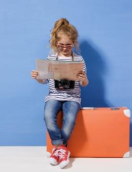 Kind blond meisje met roze vintage koffer en stadsplattegrond klaar voor zomervakantie. reizen en avontuur concept.