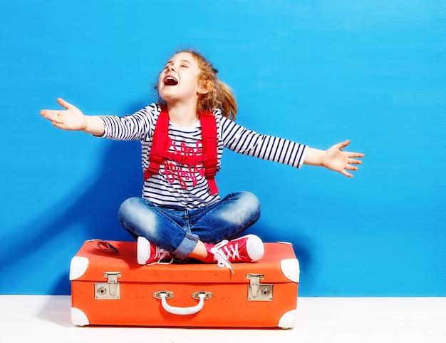 Kind blond meisje met roze vintage koffer klaar voor zomervakantie. reizen en avontuur concept.