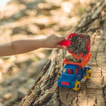 Kind buiten spelen. kid we gieten het zand in de rode vrachtwagen. kinderen straatspellen. een jongen die met een machine op het grote blok speelt
