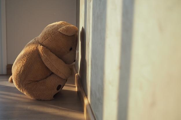 Kind concept van verdriet teddy beer vergadering leunend tegen de muur van het huis alleen, kijk droevig en teleurgesteld