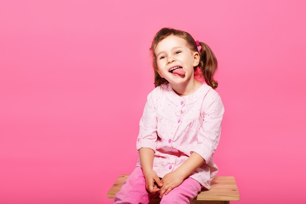 Kind dat de aap speelt. weinig babymeisje dat roze kleren draagt tegen een roze