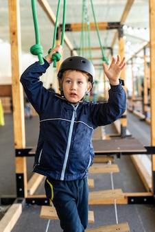 Kind dat de hindernissen van een avonturenpark probeert te overwinnen.