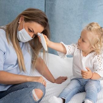 Kind dat de temperatuur van de moeder met thermometer neemt