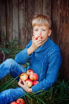 Kind dat een appel buiten in de tuin eet