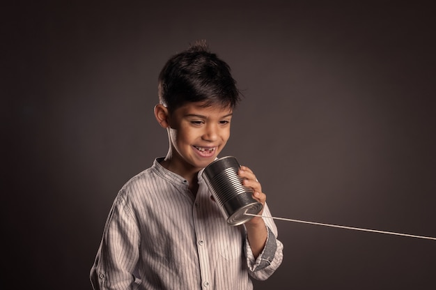 Kind dat een blik gebruikt als telefoon op grijs