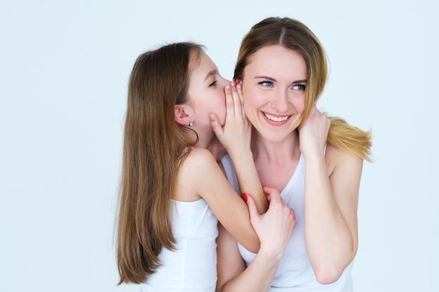 Kind dat een geheim deelt. dochter fluisterde iets in het oor van haar moeder.