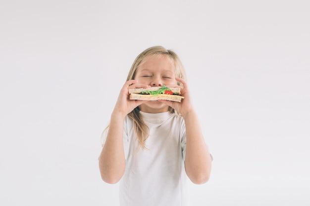 Kind dat een stuk hamburger houdt