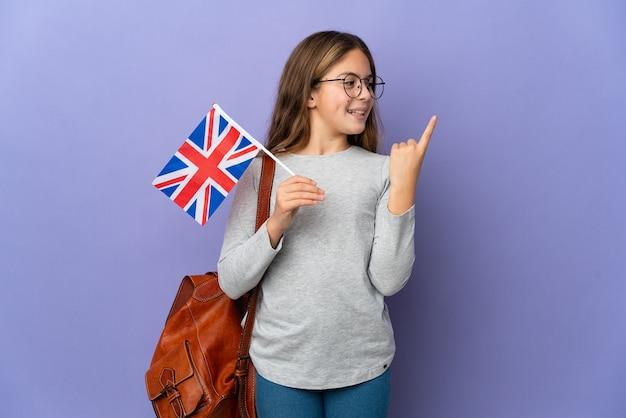 Kind dat een vlag van het verenigd koninkrijk vasthoudt over geïsoleerde achtergrond met de bedoeling de oplossing te realiseren terwijl het een vinger opheft