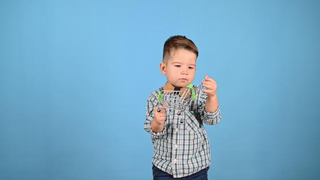 Kind dat een voedselkar houdt, op een blauwe achtergrond. hoge kwaliteit foto