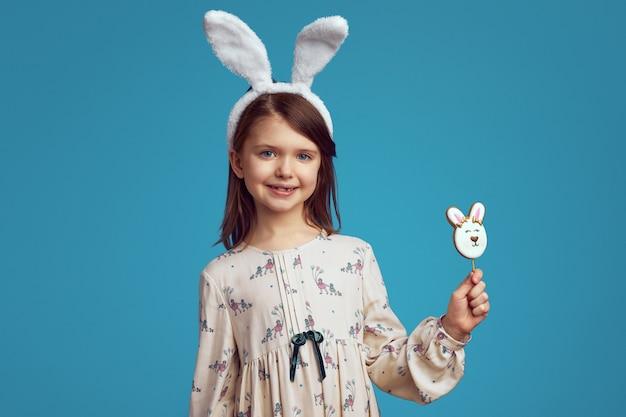 Kind dat en een koekje in vorm van konijn glimlacht houdt dat konijntjesoren draagt