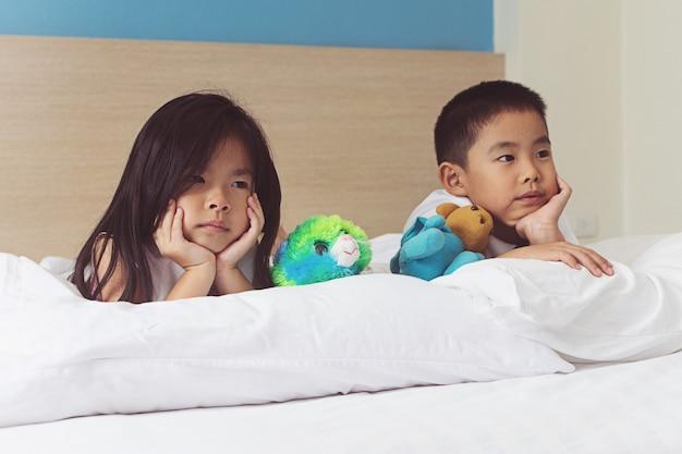 Kind dat en in het bed ontspant speelt