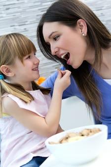 Kind dat graan met haar moeder in de keuken eet