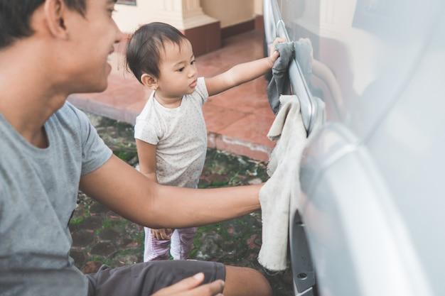 Kind dat haar papa helpt die de auto schoonmaakt