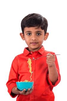 Kind dat heerlijke noedel eet, indisch jong geitje dat noedels met vork op witte ruimte eet