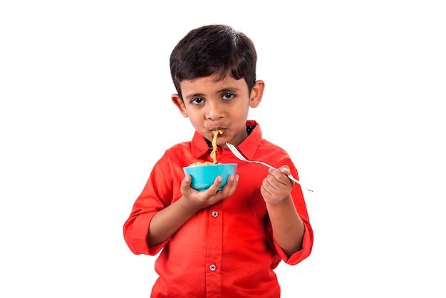 Kind dat heerlijke noedels eet, indisch kind dat noedels met vork eet