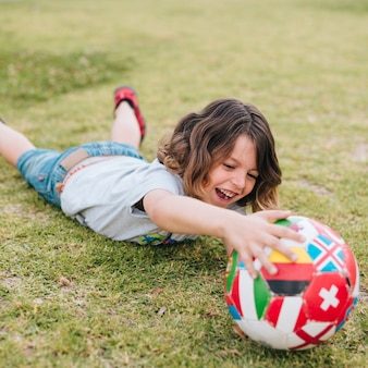 Kind dat in gras ligt en met bal speelt