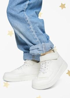 Kind dat jeans witte sneakers draagt