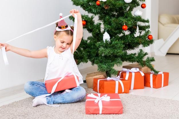 Kind dat kerstcadeautjes opent. kind onder kerstboom met geschenkdozen.