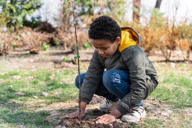 Kind dat leert hoe hij een boom moet planten