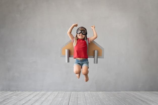 Kind dat met jetpack tegen grijze betonnen muur springt.