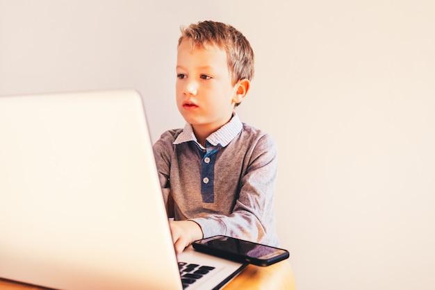 Kind dat met zijn computer in zijn zaken werkt, het geconcentreerde typen om te slagen, grappig beeld.