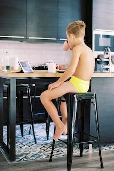 Kind dat ontbijt heeft en video's op tabletcomputer bekijkt