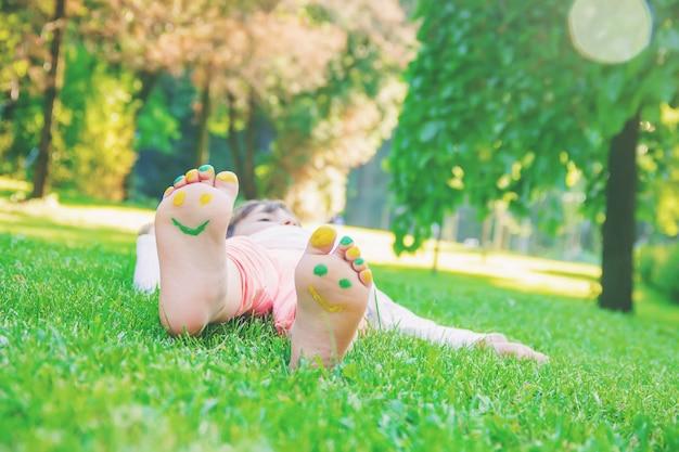 Kind dat op groen gras ligt. kind plezier buitenshuis in het voorjaar van park.