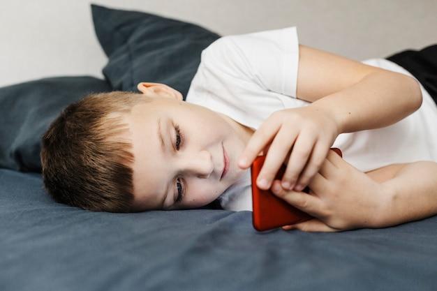 Kind dat op het bed legt en het zijaanzicht van de mobiele telefoon gebruikt