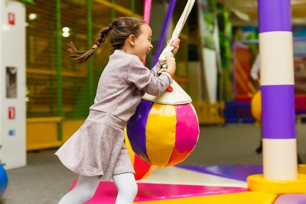 Kind dat op kleurrijke speelplaatstrampoline springt. kinderen springen in opblaasbaar springkasteel op het verjaardagsfeest van de kleuterschool