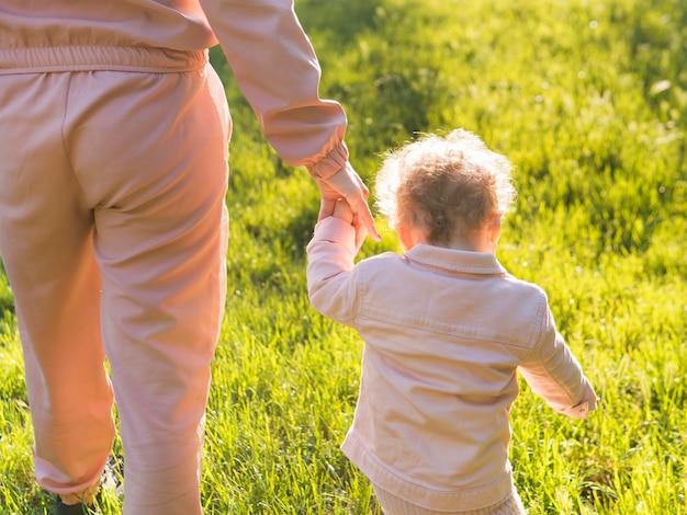 Kind dat roze kleren en mamma erachter draagt van