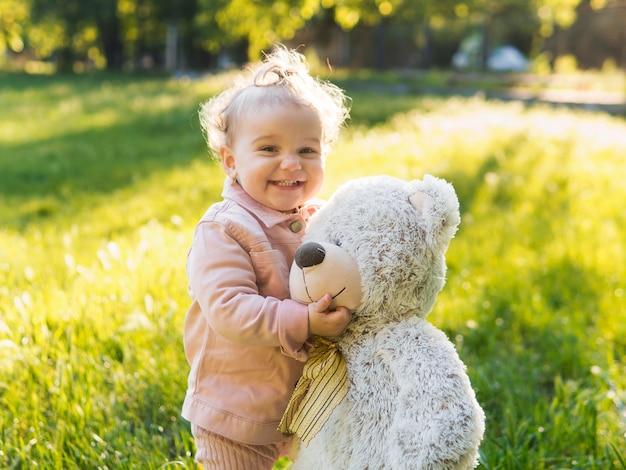 Kind dat roze kleren en teddybeer in het park draagt