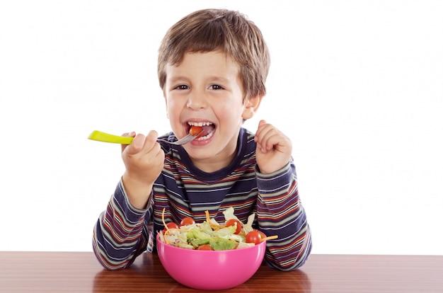 Kind dat salade a over witte achtergrond eet