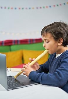 Kind dat thuis fluit leert spelen met een online leraar die met laptop is verbonden