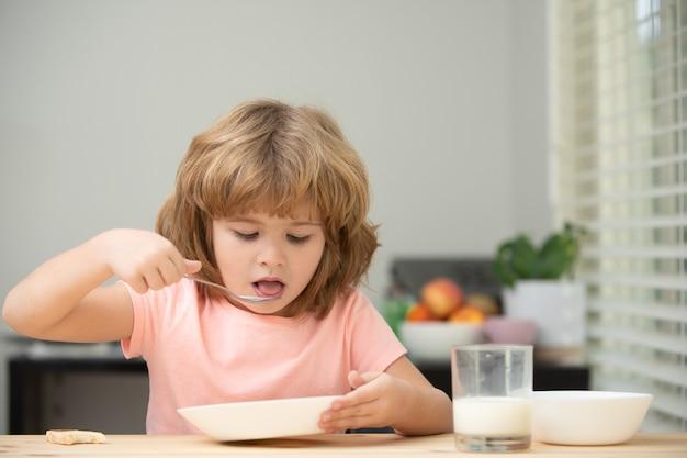 Kind dat thuis gezond voedsel eet, baby eet soep met lepel