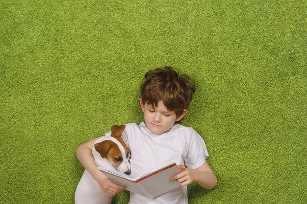 Kind dat vriendschappelijke hond jack russell omhelst las het boek