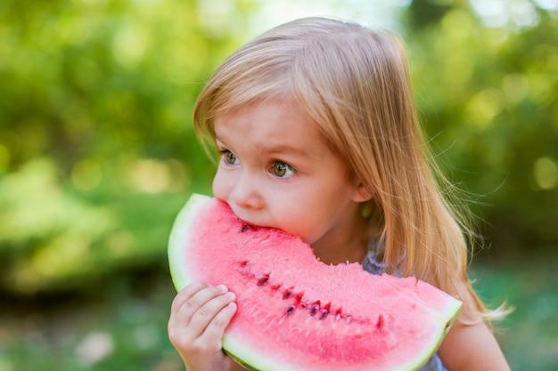 Kind dat watermeloen in de tuin eet. kinderen eten fruit buitenshuis. gezonde snack voor kinderen.