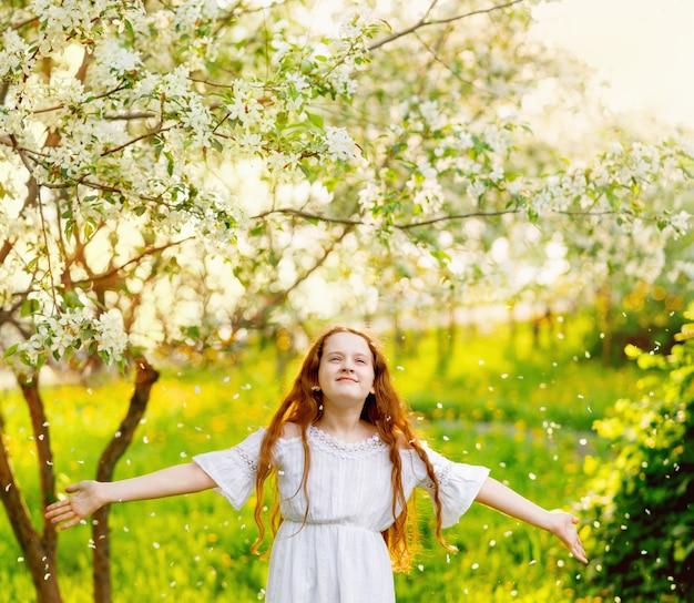 Kind dat zich onder bloemblaadjes van appelboombloemen bevindt