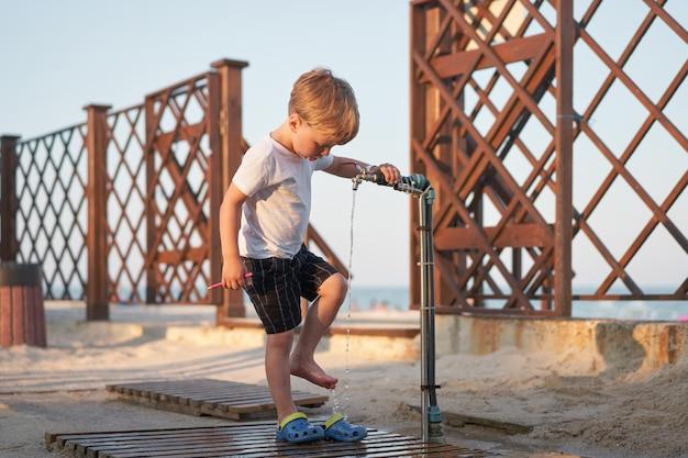 Kind dat zijn benen wast na strandzand
