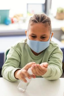 Kind dat zijn handen in de klas desinfecteert