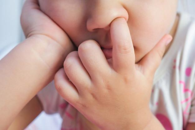 Kind dat zijn neus dicht omhoog plukt